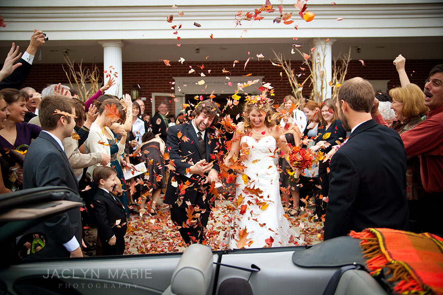 Grand exit from church with fall leaves thrown at the couple photo