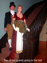 two of my guests dressed in jane austen era atire going to the ball one man with a black top hat and one woman with a feather fan both standing on our staircase