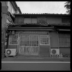 The old door (gullevek) Tags: door old sky blackandwhite building 6x6 film window japan wall clouds geotagged iso100 tokyo fuji bottles pipes bronica wires electricity   meter  aircon  housebuilding    bronicasqai fujineopanacros100  zenzabronicasqai geo:lat=35721557 geo:lon=139767691