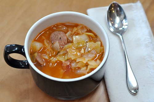 Hearty cabbage soup with spicy sausage, ham, and potatoes