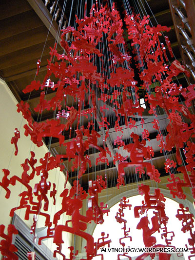 Plastic red figurines hanging from the ceiling - the figurines represent various galleries in the museums