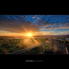 Almost a Year. ([ Kane ]) Tags: light sunset sky sun grass clouds glow lookout nsw sunburst rays kane railing bec hdr coffsharbour muttonbirdisland muttonbird gledhill solitaryisland 400d solitaryislandsmarinepark kanegledhill obramaestra soliteryisland wwwhumanhabitscomau kanegledhillphotography