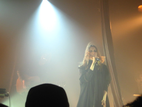Lykke Li onstage, surrounded by fog and spotlights as she sings into a microphone and her dirty-blonde hair blows over her face.
