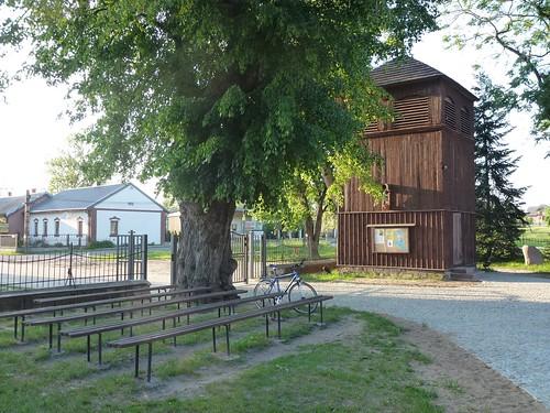 Ławki i dzwonnica przy kościele św. Wawrzyńca w Glinance