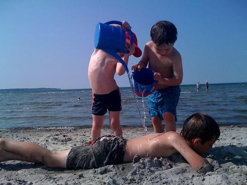 Tom och Leo sköljer av Axel. 26 grader i skuggan - skönt med en sval<br /> bris!&#8221; title=&#8221;Stranden i Farhult&#8221;  /></p> <p class=