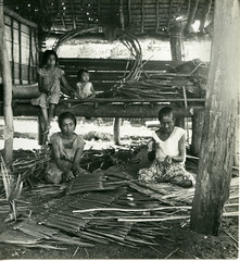 Two women weaving Nipa thatch in hut
