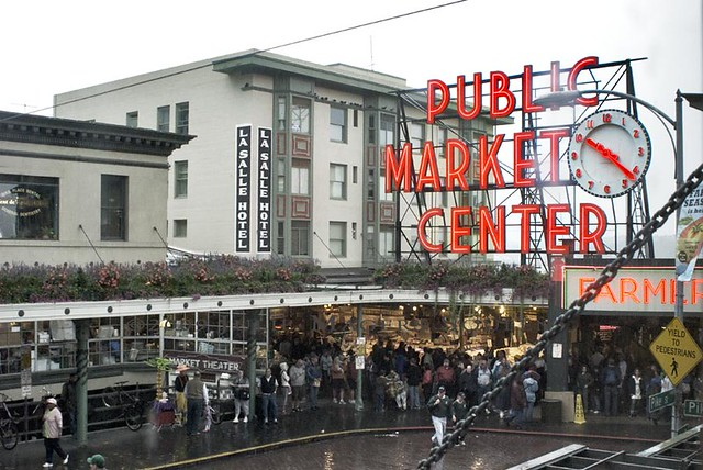 a rainy photo of the Pike Place Market in Seattle highlighting the bright red market sign and clock