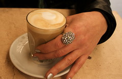 Coffee, held by female hand, painted silver nails with a silver ring