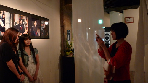 Photo of photographer Kawori Inbe taking photos of her two models in front of the photos they modelled for