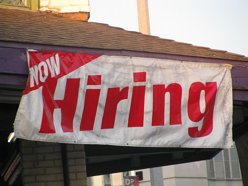 "a banner that reads ""now hiring"" at a small business"