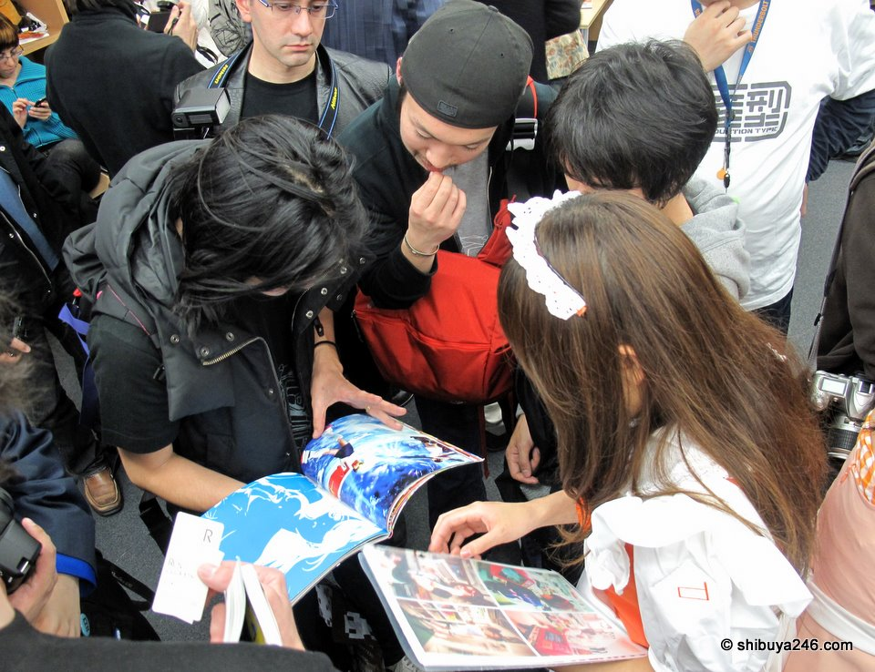 Amano Ai-san shows some of her portfolio to eager fans.