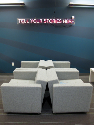 "office with neon sign saying ""tell your stories here"""
