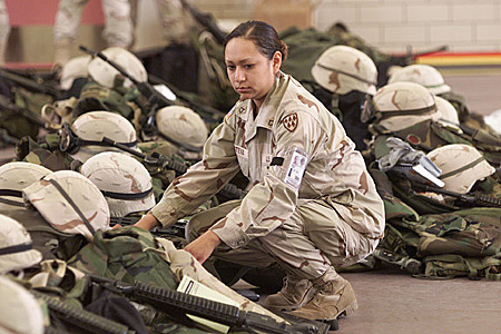 Lorie Piestewa, Operation Iraqi Freedom, circa 2000s. She is kneeling near a pile of helmets and equipment