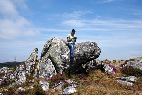 joão checks his gps coordinates sitting on an... angry turtle rock?