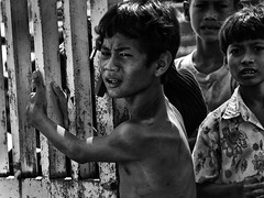 Choeung Ek, Cambodia - Children pleading for help at the gate to the Killing Field (Mio Cade) Tags: boy grave field shirt museum fence children rouge cambodia kill vietnamese khmer sad killing teeth victim political social torture murder bone sorrow genocide s21 interrogation tuolsleng kampuchea choeungek tellmeastory angka