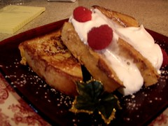 two pieces of french toast with whipped cream and red berries on top