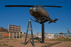 """Food's here!  Alright, corn dog?  There you go.  Diet Dr. Pepper?  Okay.  Hm... who ordered the helicopter on a stick?"" (colorblindPICASO) Tags: bird outside lightsandshadows flight cockpit bluesky pole elevated warmemorial afternoonsun armygreen bellhelicopter armyhelicopter rotorblade mineralwellstexas"