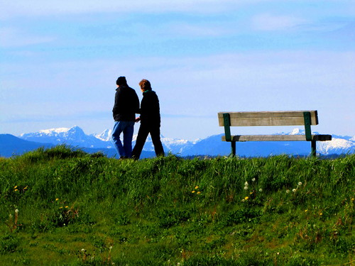 A couple walks along the dyke trail along the Middle Arm Greenway with the snow-capped northshore mountains in the back