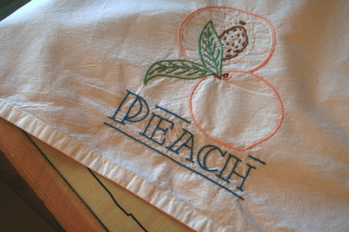 Embroidered teal towel, peach