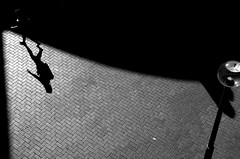On the edge of darkness (XpatScot (away)) Tags: shadow bw coffee girl walking nikon d70 streetlamp sydney australia paving darlingharbour highangle