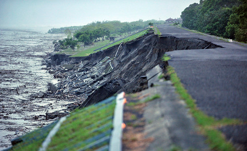Water flows past a severely eroded embankment near a damaged bridge that previously linked Pingtung and Kaohsiung, in southern Taiwan on August 9, 2009. (SAM YEH/AFP/Getty Images)