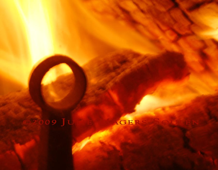 A framed photo of the heat shimmers through the glass face of the woodstove warming our home.