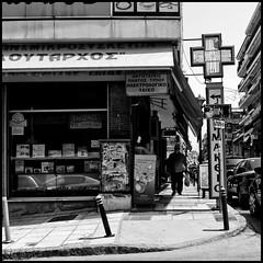 Plutarch (Georgios Karamanis) Tags: street people bw white signs man black reflection cars window glass bag square store cross pavement greece sidewalk pharmacy thessaloniki poles drugstore awnings kalamaria