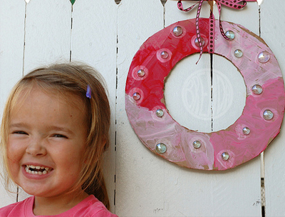 Child smiling standing next to a cardboard holiday wreath