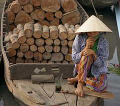 Woman on boat with wood and tea; Rach Gia, Mekong River Delta, Vietnam (Lon&Queta) Tags: people water asia hats vietnam 1995 rachgia kiengiang scanneg gpsapproximate timeincorrect