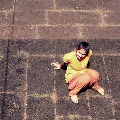 Too hot to look up... (Meera Navare) Tags: portrait people sun beach girl smile yellow stone square fun person kid sitting child uma heat meera konkan sittling challengeyouwinner toomuchheat meeranavare umanavare