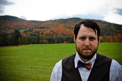 groom in brown vest and bow tie