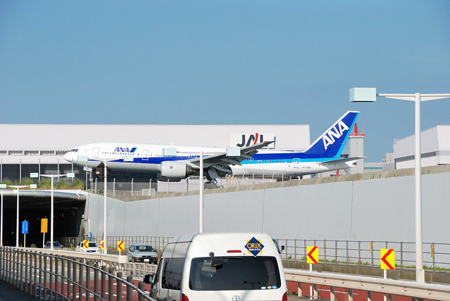 Airplane over road cars Haneda B777