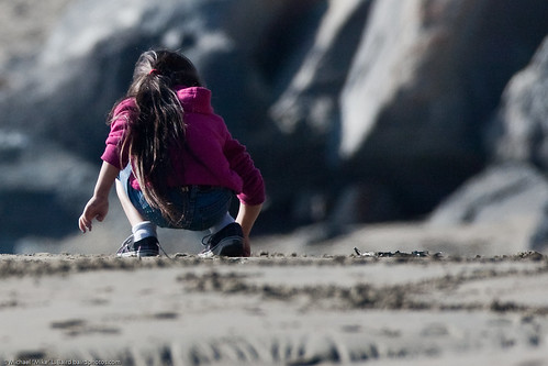 Cute little girl in pink sweater with long hair writes letters in the sand