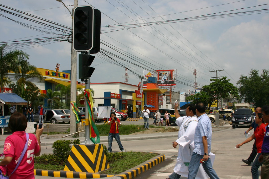 OLPGV Parish Priest Fr. Giovanni Ongcog, CP bless one of the traffic lights post.  With him are Mayor Acharon and Representative Custodio.  At the background is the 24-hour Jollibee Drive-Thru. - photo by Bariles