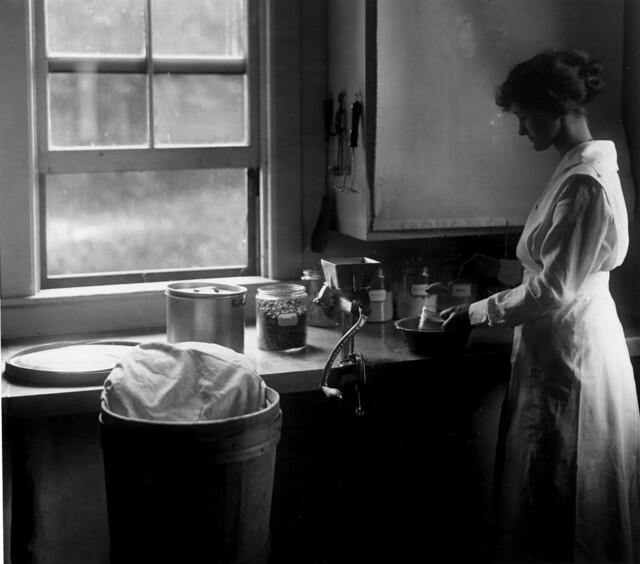 Student cooking in homemaking apartment in Lodge, 1917.