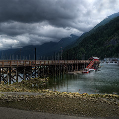 Red Shack at Horseshoe Bay (ecstaticist) Tags: ocean wood red sky cloud mist canada west building green beach water look vancouver forest photoshop canon dark georgia print square foot bay three pier boat dock sand exposure gloomy place angle natural pacific earth jetty hill shoreline dramatic rocky super columbia structure best line coastal pile shore prints convergence british gloom shack horseshoe mast straight looming province strut bcferries mountin supernatural masted bcferry 3x darkeness tonemapped tonemapping g10 photmatix footprinttree attheendyouwonionlyfor4hoursyouallday