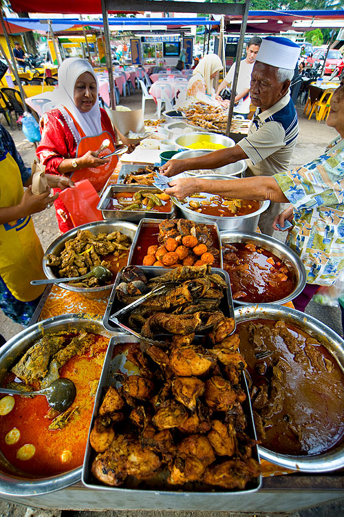 Dishing up dishes to go at an evening market on the eve of Aidilfitri, Kota Bharu, Malaysia