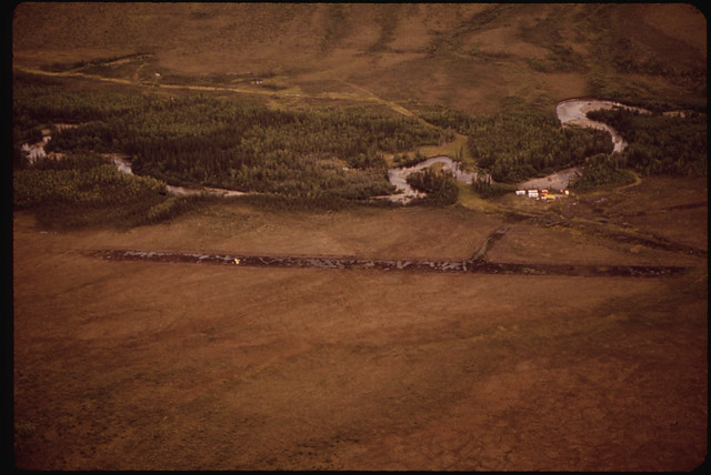 Abandoned Trailers and a Wrecked Plane on the Eroded Remains of a Winter Ice Strip (Near Mile 295)081973 by The US National Archives
