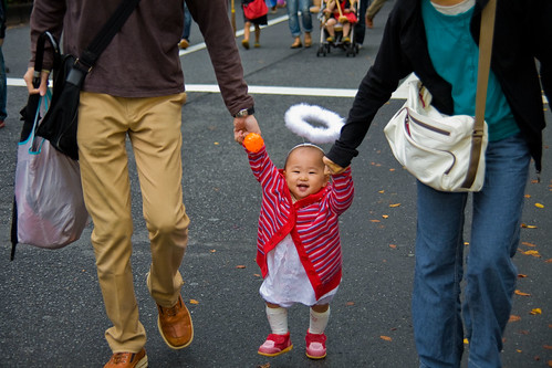Feather-haloed first-stepper teeters thru Omotesando Halloween Parade by Buz Carter.