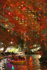 cruising under a canopy of light (jmtimages) Tags: christmas city autumn trees people urban holiday fall water colors sanantonio automne canon reflections festive season lights downtown december mood texas outdoor atmosphere tourist 7d 2009 barge riverwalk decembre saison nel