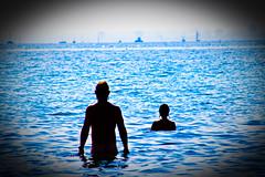 Bathers (Tom Brasch) Tags: toronto ontario beach point boats lomo lomography couple horizon highcontrast lakeontario candids shootfromthehip hanlans saturatedcolors saturatedcolours nudebathers