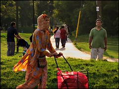 moment at Dentonia Park (Now and Here) Tags: park street light red orange woman toronto ontario canada color colour green grass canon hair dress wind fb path robe candid headscarf hijab blow powershot explore pathway lateafternoon mostviewed crescenttown dentoniapark dentonia fave10 explore342 sx110is nowandhere