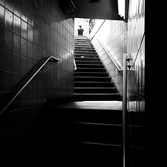 Exit Light (ecstaticist) Tags: new york city nyc newyorkcity travel urban blackandwhite bw white holiday black reflection stone stairs train photoshop canon underground subway tile island climb stair shine angle conversion manhattan district steel rail pedestrian polish commuter exit lower financial stainless upward g10
