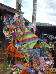 A kite seller on the side of the road.
