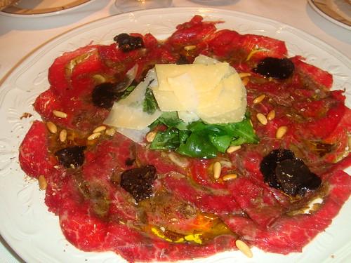 Carpaccio de solomillo relleno con hongos, pequeña ensalada de rúcula y parmesano