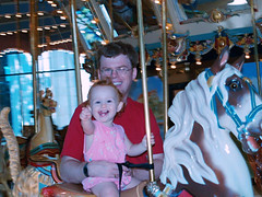 Speck on a carousel horse, waving at Papou