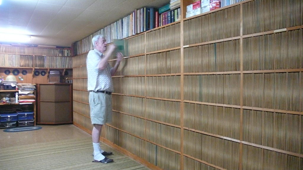 Joe pulls a record from 30,000. He has no shelving labels - he knows the location of each of his records through memory.