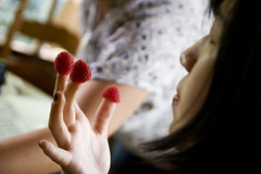 plucking raspberries off her fingers