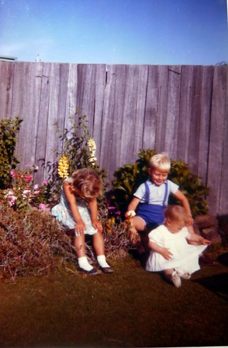 me with my head down being teased by my cousin , my little sister is sitting on the grass, 1963