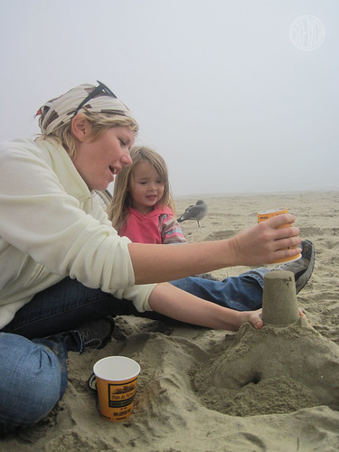 Deb showing Bug how to make a sand castle with a coffee cup